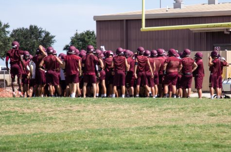 Varsity football team comes together for a  huddle at practice.